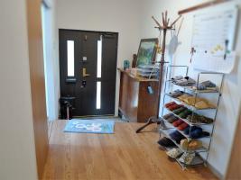 NPO法人「学生支援ハウスようこそ」が運営するシェアハウス。家庭的な雰囲気の玄関まわり。玄関ドアは、かつては引き戸だった